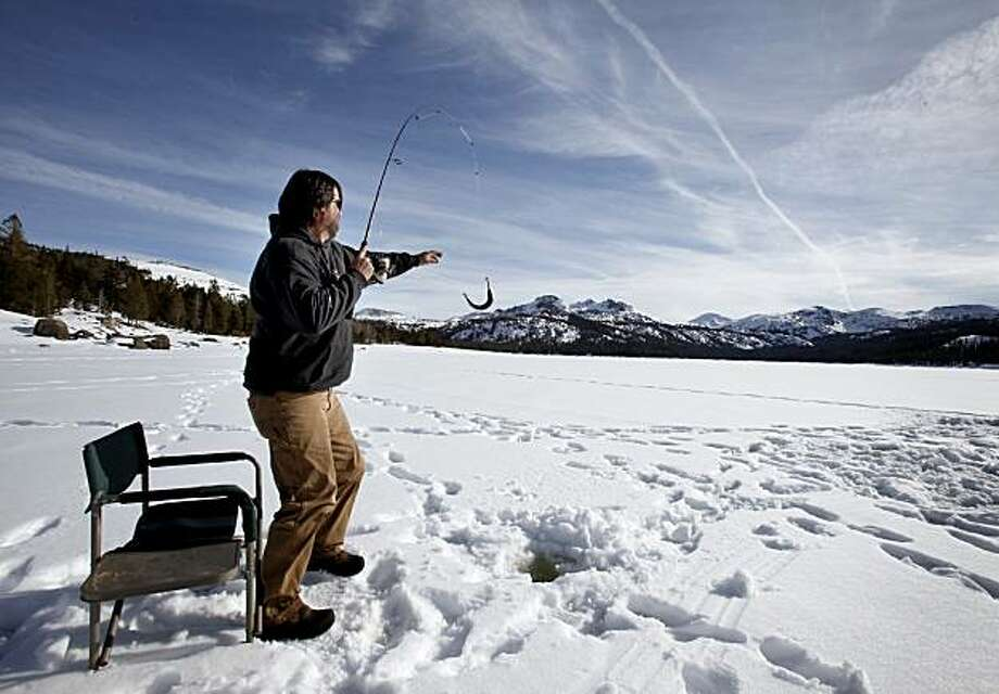 At Caples Lake in Alpine County, Anthony Stark caught an undersized trout on his first try at ice fishing.  Stark lives nearby and is under employed. Alpine County, the California county with the lowest population, also lost the most percentage of people recently, causing problems inherent with rural counties around the state. Photo: Brant Ward, The Chronicle