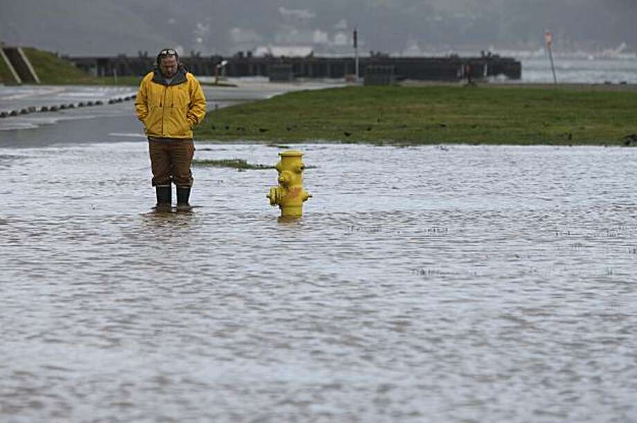 During a calm in the first of several storms expected to hit the Bay Area, Andrew Baird of the Presidio Trust checks on a drainage problem on Mason Street near Crissy Field on Monday. Photo: Mike Kepka, The Chronicle