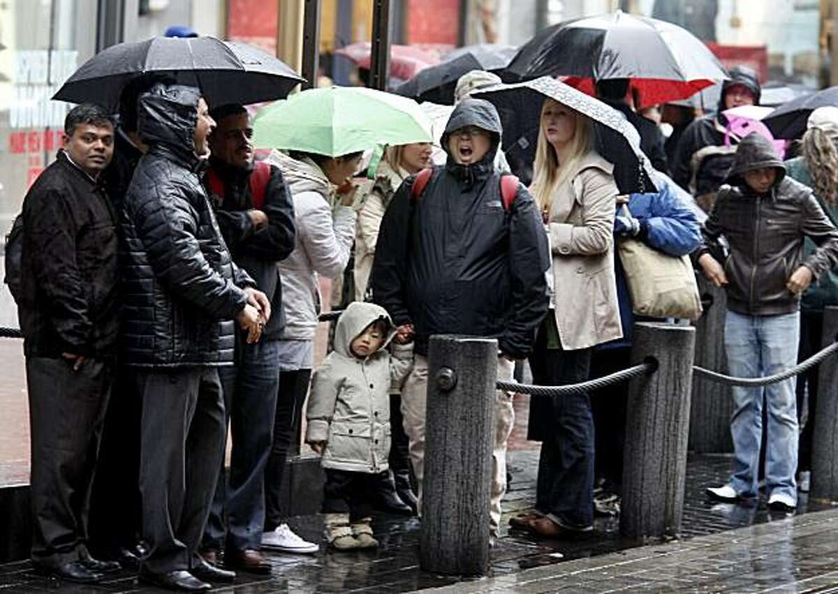 People in line at Powell and Market streets wait patiently in the rain for the cable car. The predicted storms for the week began Sunday, but rainfall was sporadic in downtown San Francisco during the afternoon.