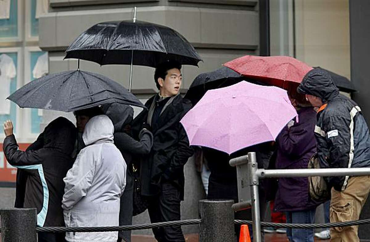 People in line at Powell and Market streets for the cable car huddle beneath their umbrellas during a brief downpour. The predicted storms for the week began Sunday, but rainfall was sporadic in downtown San Francisco during the afternoon.