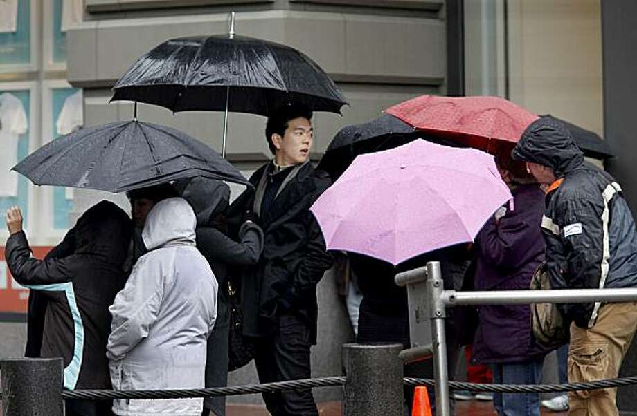 People in line at Powell and Market streets for the cable car huddle beneath their umbrellas during a brief downpour. The predicted storms for the week began Sunday, but rainfall was sporadic in downtown San Francisco during the afternoon. Photo: Brant Ward, The Chronicle