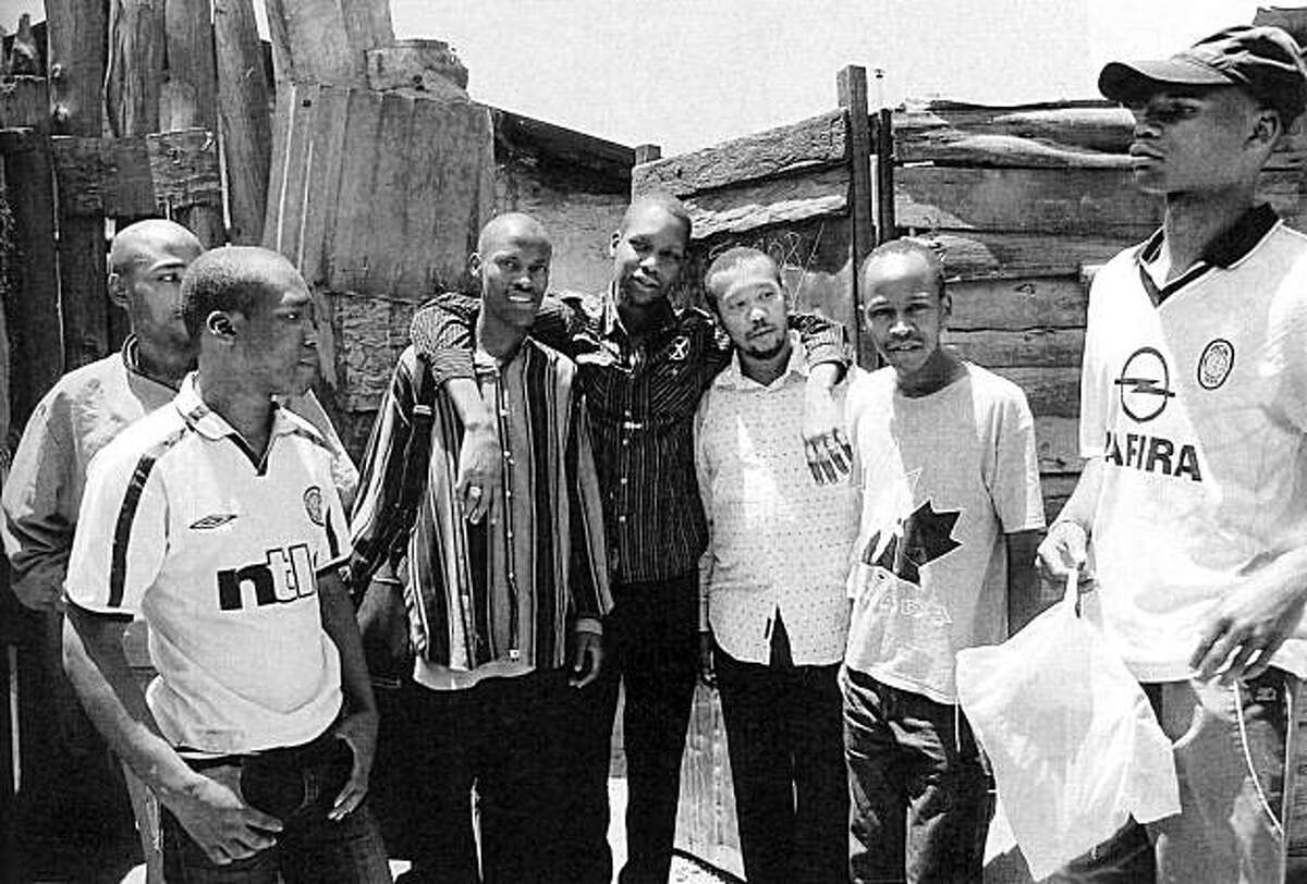 """George Obama, center, in the gateway to his Huruma home, with """"some of my ghetto buddies."""" On his right is Clyde Kagondu, a Kenyan Tae-Kwon Do champion. """"Clyde and I run tae kwon do classes for the ghetto kids in an effort to build their respect and self-esteem"""""""