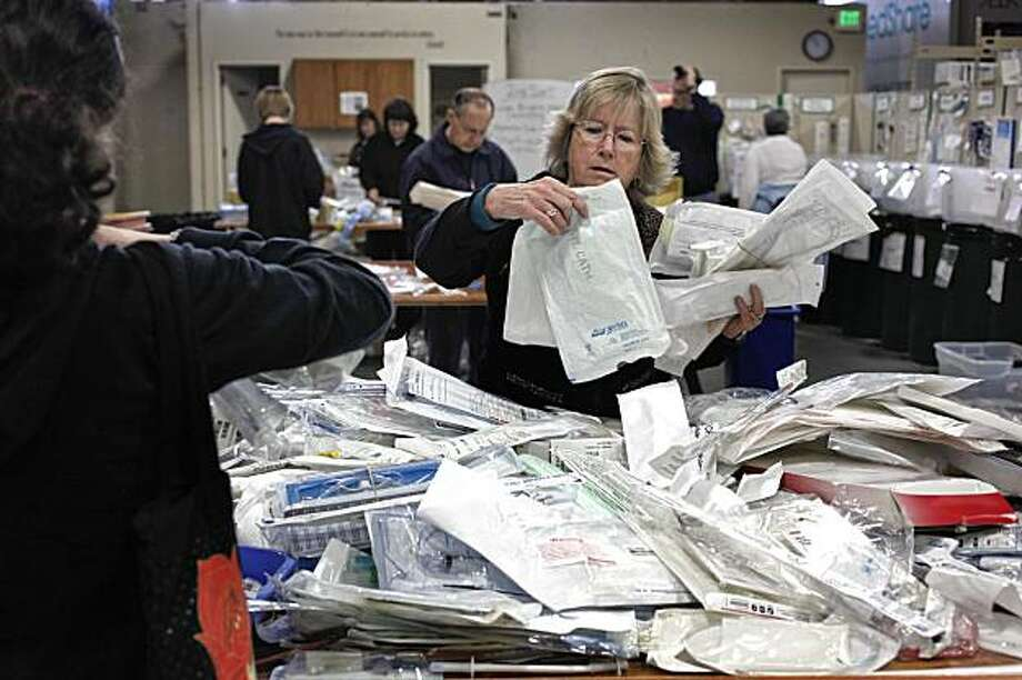 Volunteer Mavis McCombs, with Catholic Community of Pleasanton, sorts through piles of catheters that will be repackaged and shipped to Haiti at the MedShare warehouse in San Leandro, Calif. on Saturday January 16, 2010. MedShare, an Atlanta based organization that ships surplus medical supplies around the world, has opened a second office in San Leandro where they are preparing their fourth shipment to the earthquake devastated Island of Haiti. Photo: Michael Macor, The Chronicle