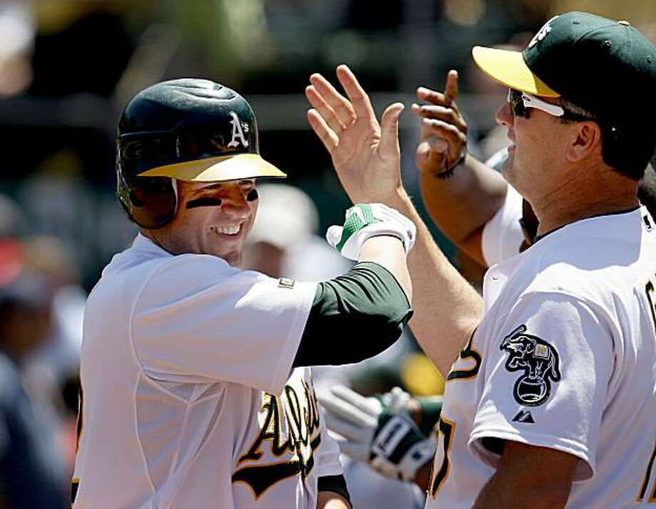 Jack Cust is greeted in the dugout after his grand slam in the fourth inning including manager Bob Geren (right). The A's defeat the Rangers 9-4. The Oakland Athletics vs. the Texas Rangers at the Oakland Coliseum Thursday May 7, 2009. Photo: Brant Ward, The Chronicle