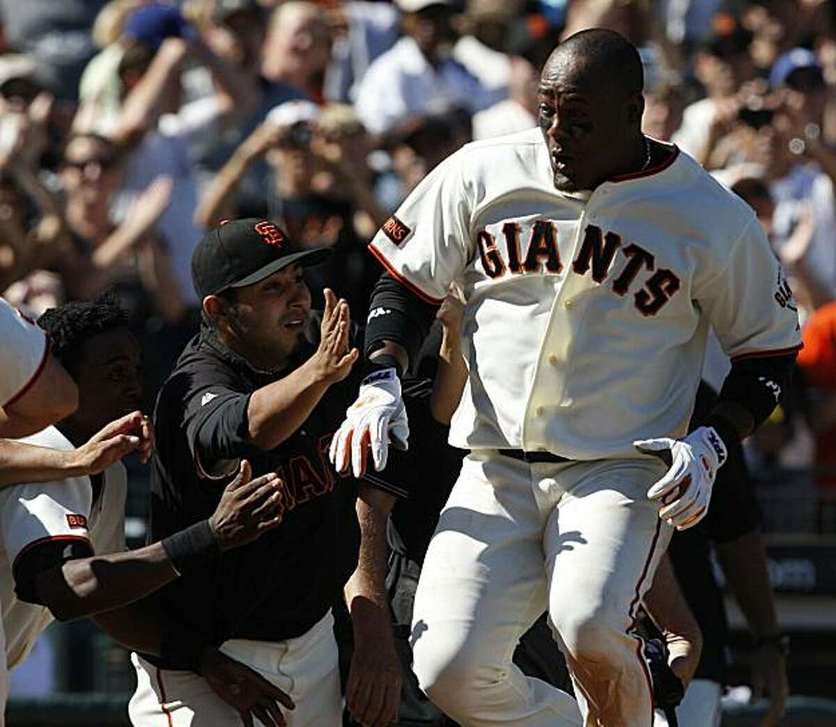 San Francisco Giants Juan Uribe jumps on home plate surrounded by his teammates after hitting a walk-off homer in the 10th inning to beat the L.A Dodgers 4-2 at AT&T in San Francisco, Calif., on August 12, 2009.