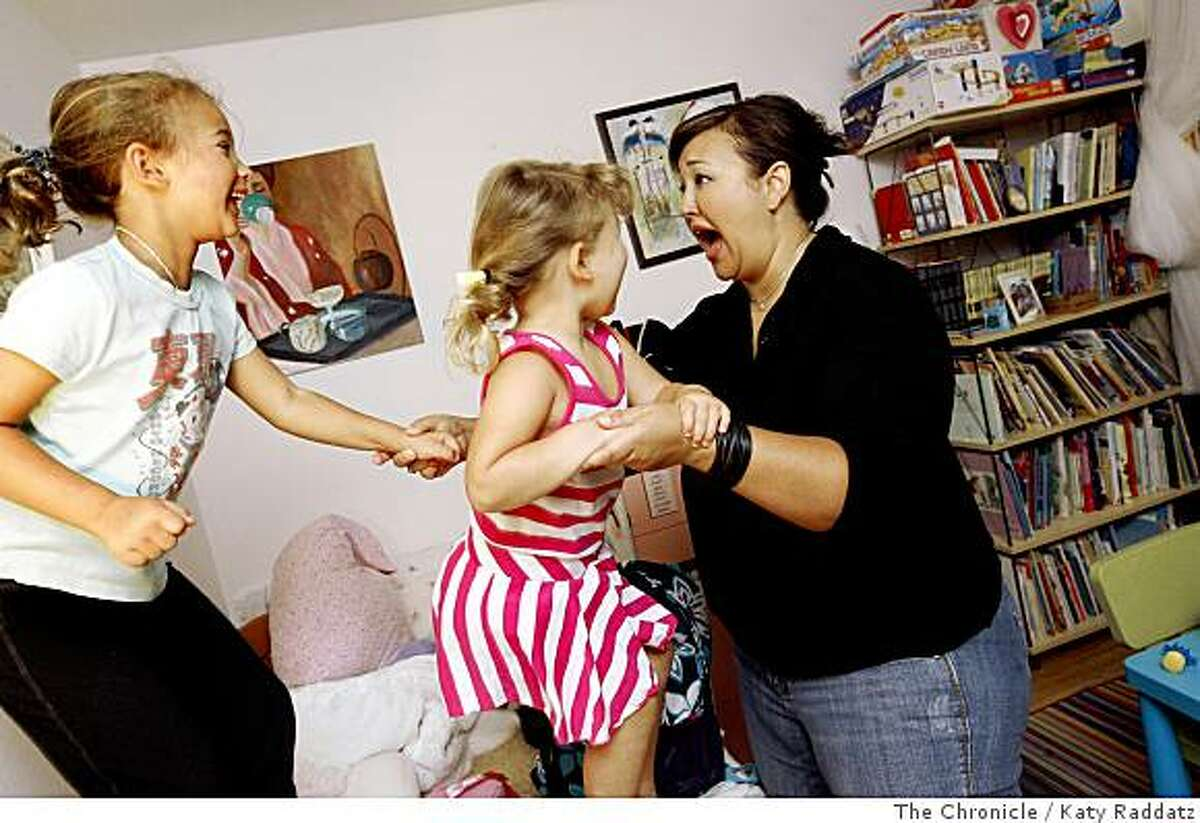 Stefania Pomponi Butler, right, who just spent three days at the BlogHer Conference, a very successful blogger writing about housewifely topics, politics, and culture on blogs MOMocrats and Kimchi Mamas, says the best thing about being able to work from her home is spending time with her daughters Bunny, age 6, left, and Wallie, age 3, center, jumping on the bed, in Palo Alto, Calif. on Monday, July 21, 2008.Photo by Katy Raddatz / The Chronicle