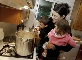 Lizzie holds Ben (left) and Zaidie as they look at the almost finished soup. Lizzie Binder is chef at Bar Bambino, she prepares Minestra Maritata, a simple soup that combines many cuts of meat at her home in Napa. She is joined by family members Ben, who is three years and Zaidie, who is 10 months.