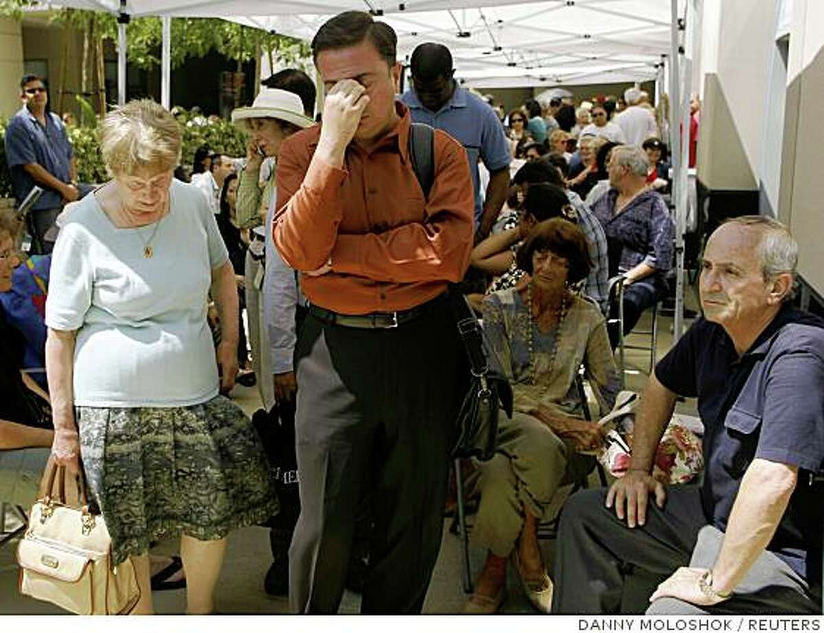 Robert Buscemi (C) reacts at the front of the line after waiting six hours to enter an IndyMac Bank branch under federal regulation management at the company's corporate headquarters in Pasadena, California July 14, 2008. Regulators seized Pasadena-based IndyMac on Friday after a bank run in which customers withdrew $1.3 billion of deposits over 11 business days, as worries about the company's survival grew, regulators said. REUTERS/Danny Moloshok (UNITED STATES)