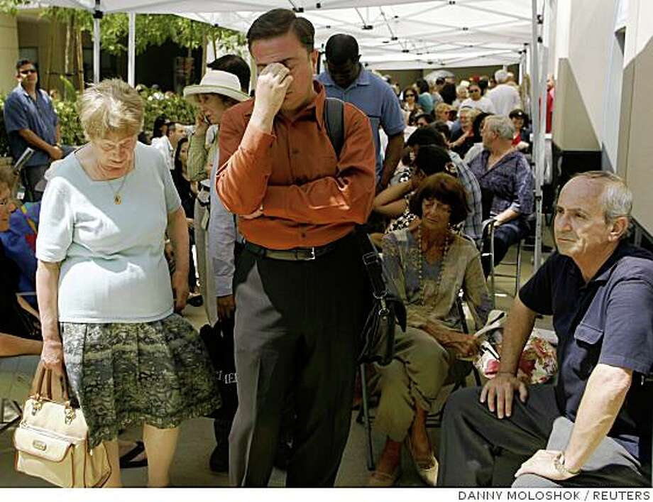 Robert Buscemi (C) reacts at the front of the line after waiting six hours to enter an IndyMac Bank branch under federal regulation management at the company's corporate headquarters in Pasadena, California July 14, 2008. Regulators seized Pasadena-based IndyMac on Friday after a bank run in which customers withdrew $1.3 billion of deposits over 11 business days, as worries about the company's survival grew, regulators said. REUTERS/Danny Moloshok (UNITED STATES) Photo: DANNY MOLOSHOK, REUTERS