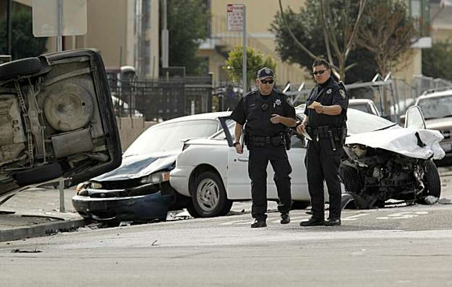 Oakland Police chased a vehicle traveling at a high rate of speed at about 10:30 am this morning, which ended as a three vehicle accident, with a 63 year old woman traveling as a passenger in the white car being killed and the suspect's vehicle overturned, at the corner of 62nd Ave. and Foothill Blvd., in Oakland, Ca. on Thursday December 31,2009. Photo: Michael Macor, The Chronicle