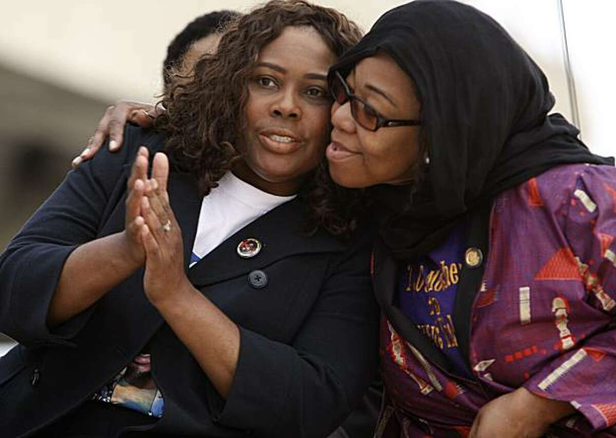 The mother of Oscar Grant, Wanda Johnson, (left) gets a hug from Lorrain Taylor as they join a crowd of family, friends and supporters for a vigil to remember her son, at the Fruitvale BART station on Friday January 1, 2010, in Oakland, Ca., a year after Grant was shot and killed early New years Day 2009.