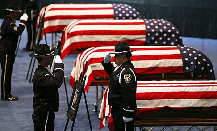 Oakland Police honor guard members exchange posts next to the flag-draped caskets of Oakland Police Officers Sgt. Mark Dunakin, 40; John Hege, 41; Sgt. Ervin Romans, 43; and Sgt. Daniel Sakai, 35, are carried by law enforcement officers into Oracle Arena on Friday, Mar. 27, 2009, in Oakland, Calif. Thousands of officers and firefighters from around the nation and overseas along with mourners turned out for Friday's funeral for the four veterans. The four officers were shot in the line of duty Saturday, March 21. (Michael Macor/ San Francisco Chronicle, Pool) Photo: Michael Macor, The Chronicle