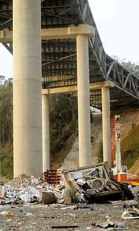 The crumpled remains of a big rig lie beneath the San Francisco-Oakland Bay Bridge on Monday, Nov. 9, 2009, in San Francisco, following an early morning crash. The truck's driver died after losing control on the bridge's temporary S-curve and crashing to the ground several hundred feet below. (AP Photo/Noah Berger) Photo: Noah Berger, AP