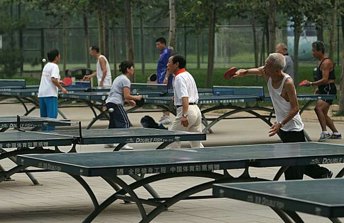 Dozens turn out early morning for a little table tennis action on the grounds of Sun Park in North Eastern Beijing, China on Tuesday Aug. 5, 2008.