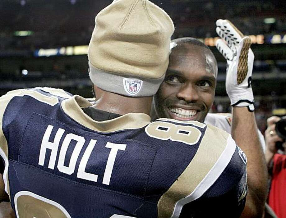 FILE - In this Dec. 21, 2008 file photo, San Francisco 49ers wide receiver Isaac Bruce right, gets a hug from former teammate St. Louis Rams wide receiver Torry Holt after an NFL football game Sunday in St. Louis. Isaac Bruce's final NFL game might be back in the very place where he spent his most productive years. head coach Mike Singletary said the 37-year-old Bruce's mates approached the coach to say they wanted the 16th-year veteran to play Sunday at St. Louis in the team's last game. (AP Photo/Jeff Roberson, File) Photo: Jeff Roberson, AP