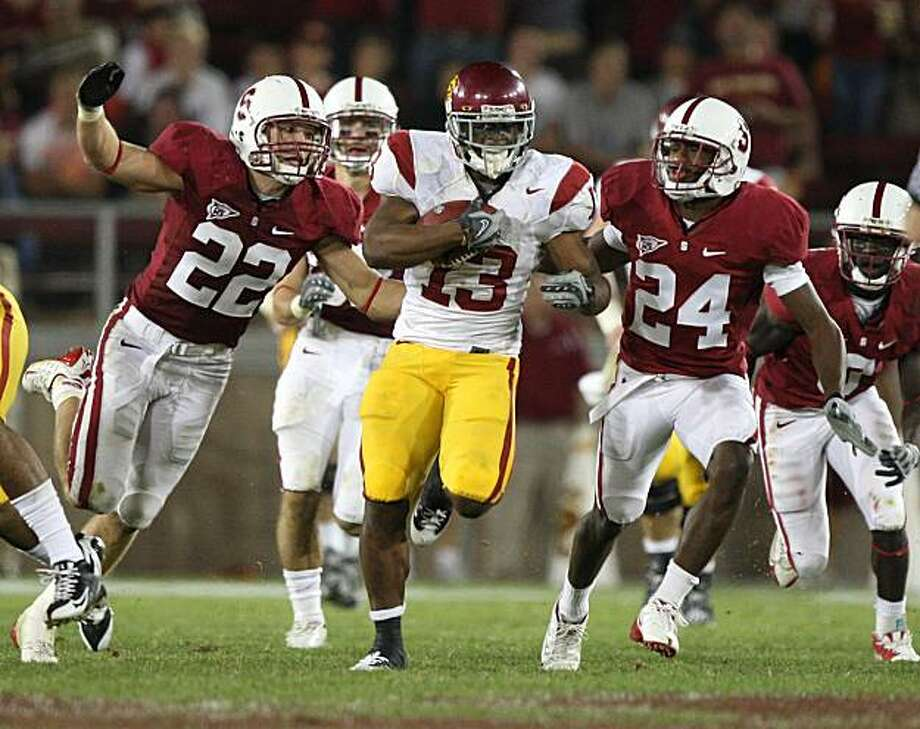 STANFORD, CA - NOVEMBER 15:  Stafon Johnson #13 of USC Trojans runs against Bo McNally #22 and Kris Evans #24 of the Stanford Cardinals in the first half at Stanford Stadium on November 15, 2008 in Stanford, California.  (Photo by Jed Jacobsohn/Getty Images) Photo: Jed Jacobsohn, Getty Images