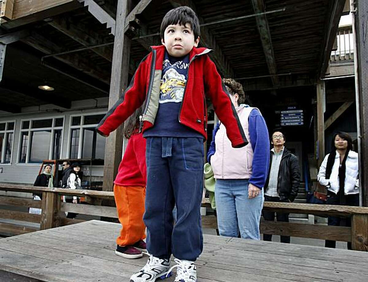 Myles Gong, 5, from Menlo Park could only shrug when he could see no sea lions. The sea lions have disappeared from Pier 39 in San Francisco.