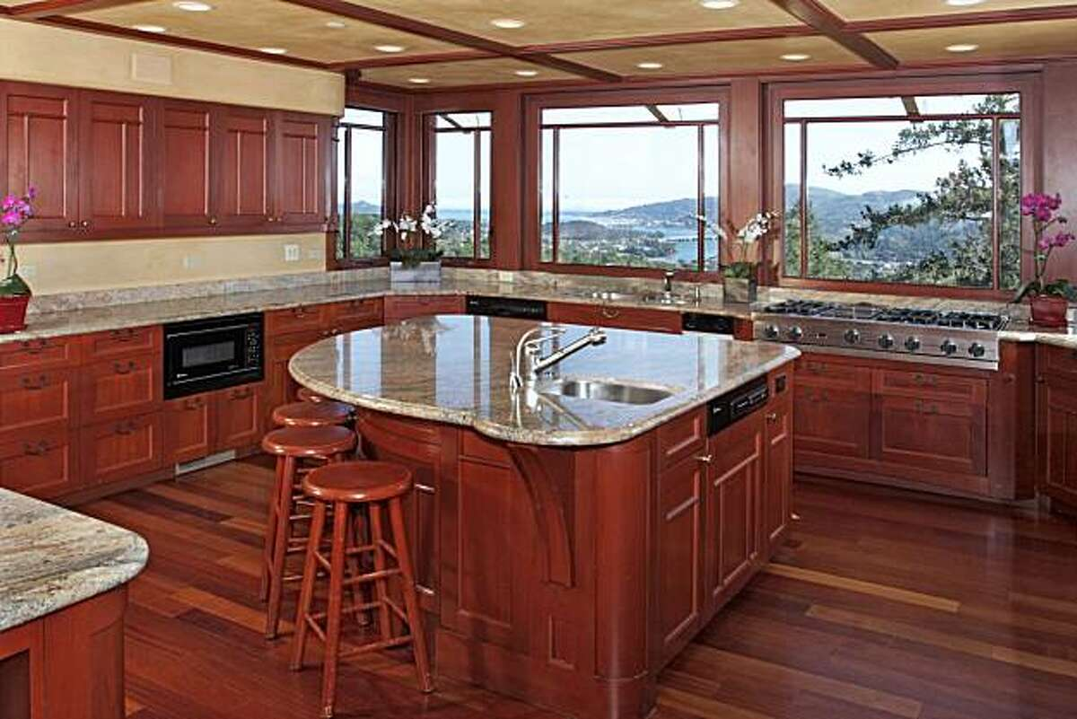 The wrap-around kitchen with recessed lighting and an island with bar area. Like most of the rooms in the house, the kitchen was designed to accomodate the property's prominent vistas.