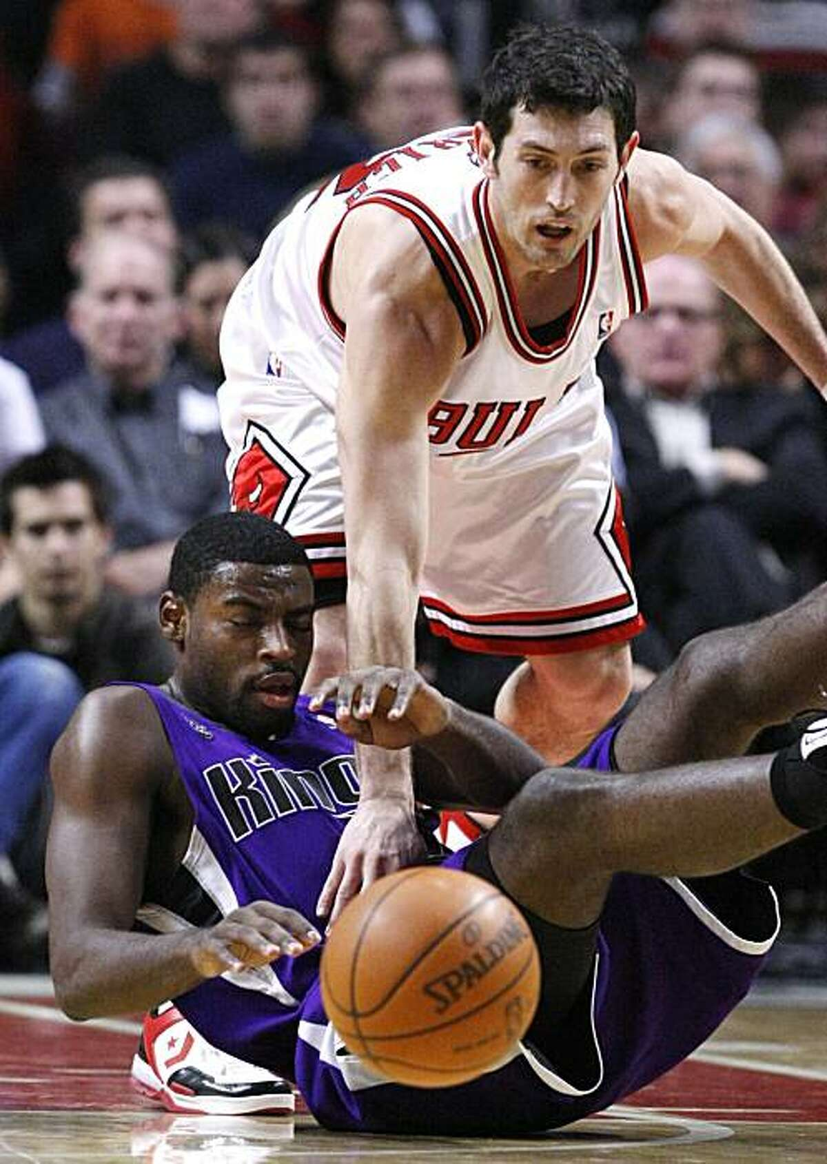 Chicago Bulls guard Kirk Hinrich, top, battles Sacramento Kings guard Tyreke Evans for a loose ball during the first half of an NBA basketball game Monday, Dec. 21, 2009, in Chicago. (AP Photo/Charles Rex Arbogast)