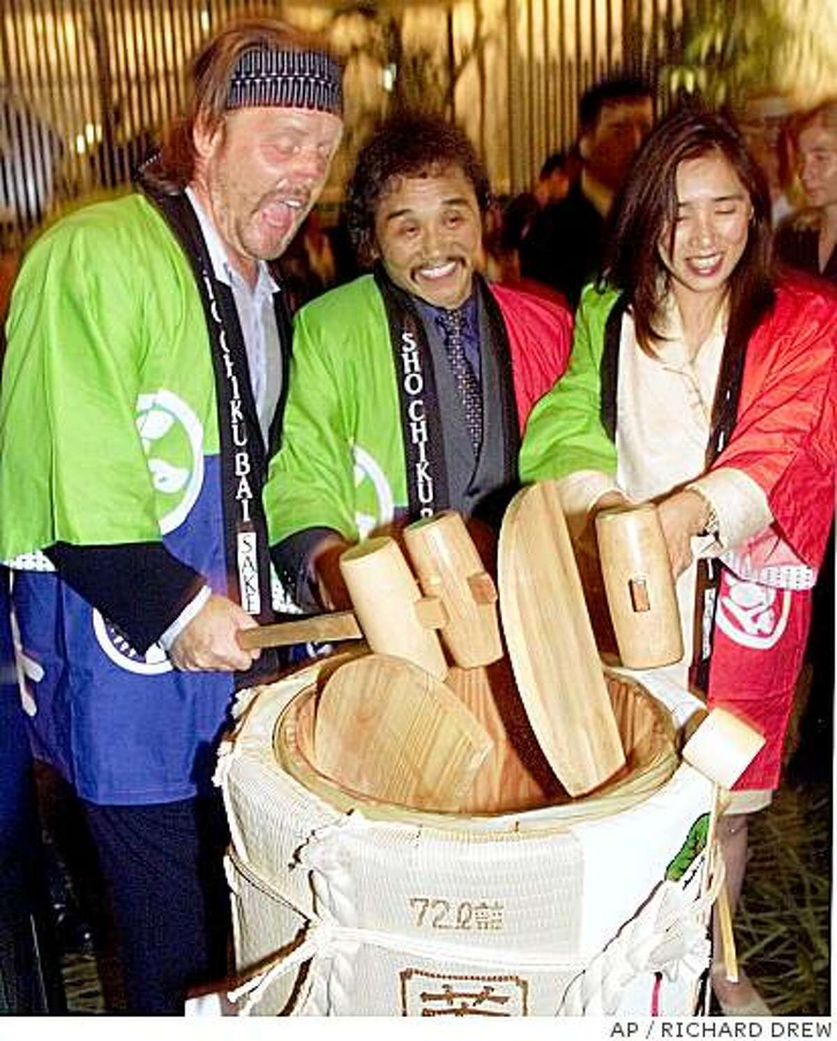 ** FILE ** This Thursday, Aug. 9, 2001 file photo shows Rocky Aoki, center, restaurateur, former athlete and founder of the Japanese steakhouse chain Benihana Inc., as he cracks open a ceremonial cask of sake with the help of co-owner Barbara Matsumura and the restaurant's architect Chris Smith, celebrating the opening of one of his ventures, Haru, in New York. Aoki, who strived to offer diners a sense of magic and entertainment at his Japanese steakhouse Benihana, died Thursday, July 10, 2008 in New York after complications from cancer. He was 69. (AP Photo/Richard Drew, File)