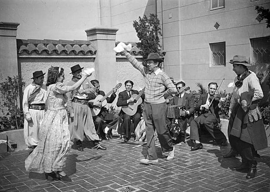 As part of the 1941 research trip to gather story material, Walt Disney joins the dancers from Andres Chazarreta's folkloric group on the rooftop of Buenos Aires' Alvear Palace Hotel. The dancer on the far right, Miguel Gramajo, was found during research and shares his memories of that afternoon in Walt & El Grupo. Photo: Courtesy Of Disney
