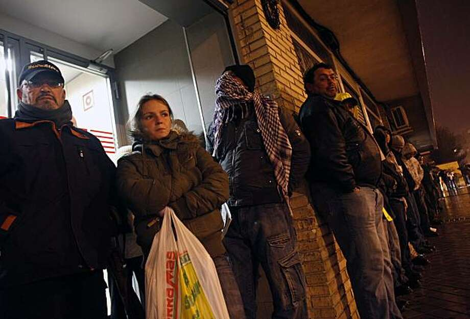 People line up before dawn at an employment office in Madrid, Spain, December 23, 2009. Many workers aged 16 to 24 who took jobs when the Spanish economy was healthy are now out of work as the unemployment rate for the group nears 43 percent. (Eric Thayer/The New York Times) Photo: Eric Thayer, NYT