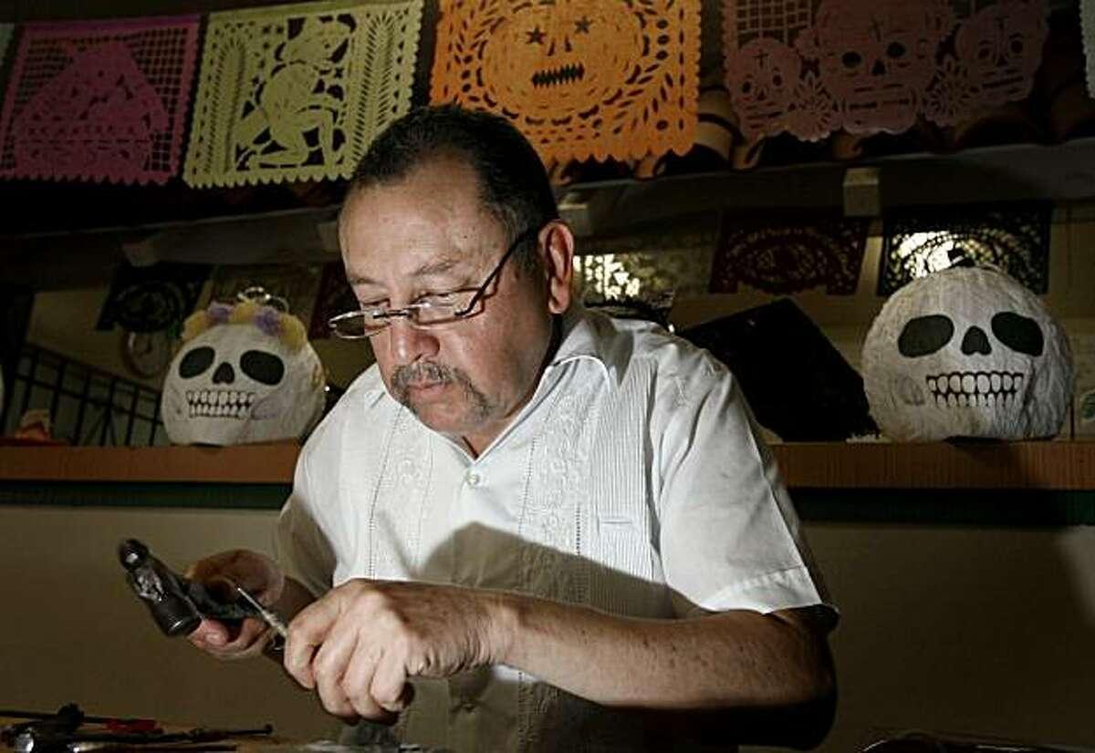 Enrique Matinez, demonstrates how to make decorative paper at the La Borinquena Mex-icatessen in Oakland Calif. on Saturday October 31, 2009.