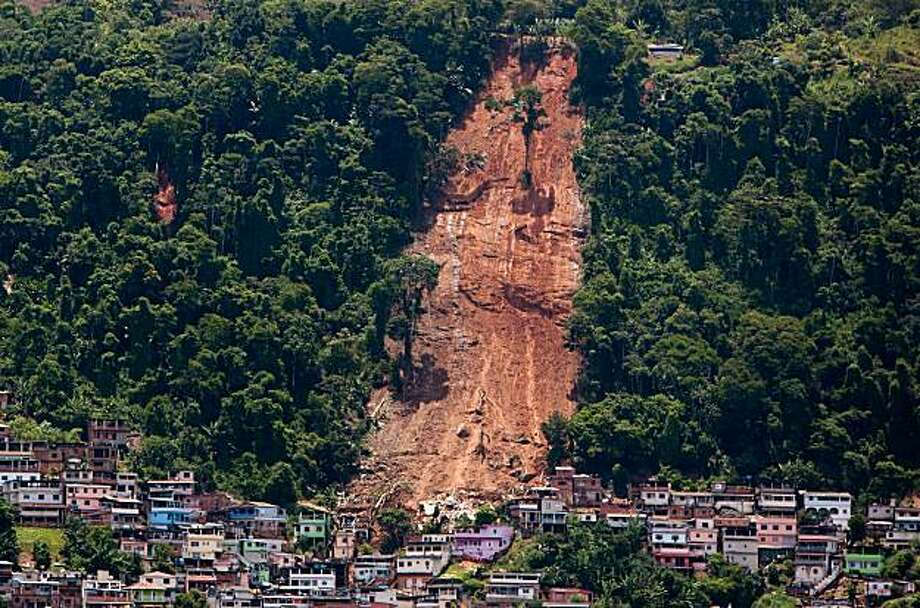 A mountainside is bare after a mudslide in Morro da Carioca, an area in the city of Angra dos Reis, near Rio de Janeiro, Brazil, Saturday, Jan. 2, 2010.  A rain-soaked hillside collapsed on homes after New Year celebrations early Friday in Angra dos Reis killing at least 12 people. A separate mudslide on the nearby island of Ilha Grande killed at least 22. (AP Photo/Felipe Dana) Photo: Felipe Dana, AP
