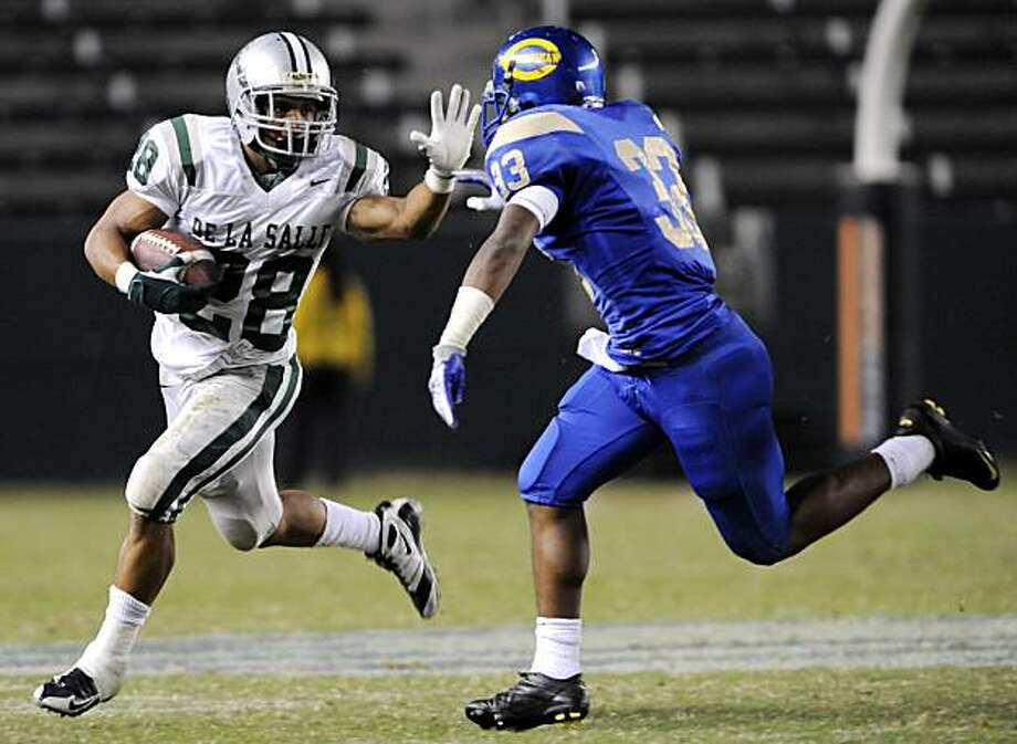 De La Salle's Terron Ward, left, stiff-arms Crenshaw's Geoffrey Norwood in the second quarter during the 2009 CIF Open Division State Bowl Game between De La Salle High School and Crenshaw High School at the Home Depot Center in Carson on Saturday. Photo: Carlos Delgado, Special To The Chronicle