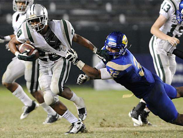 De La Salle's Terron Ward, left, evades the tackle by Crenshaw's Hayes Pullard in the third quarter during the 2009 CIF Open Division State Bowl Game between De La Salle High School and Crenshaw High School at the Home Depot Center in Carson, Calif., on Saturday, Dec. 19, 2009. Photo: Carlos Delgado, Special To The Chronicle