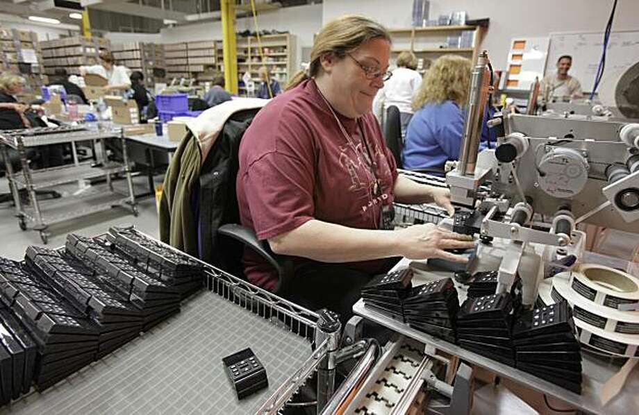 In this photo made Monday, Dec. 14, 2009, Kim Robinson puts labels on Playaway self-contained, battery-powered audio player books at the Findaway World headquarters in Solon, Ohio. Manufacturing activity grew in December at the fastest pace in more than three years, a sign that the pace of the economic recovery is picking up, a private trade group said Monday, Jan. 4, 2010. (AP Photo/Amy Sancetta) Photo: Amy Sancetta, AP