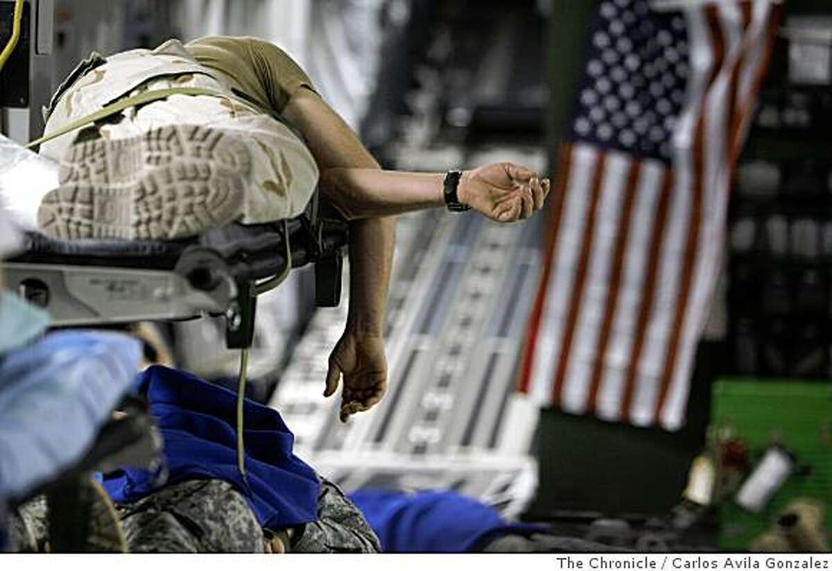 A wounded marine lies on a litter in the cargo area of a C-17 Globemaster as he and other combat wounded are transported from Bagram Air Base in Afghanistan to Ramstein Air Base in Germany for further treatment on Sunday, June 21, 2008. The C-17 is assigned to the 60th Air Mobility Wing at Travis Air Force Base, flown by a crew from the 349th Air Mobility Wing, a reserve associate wing which augments the 60th. Both wings work together as partof the Total Force, flying missions as required by Air Mobility Command and Department of Defense.Photo by Carlos Avila Gonzalez / The Chronicle