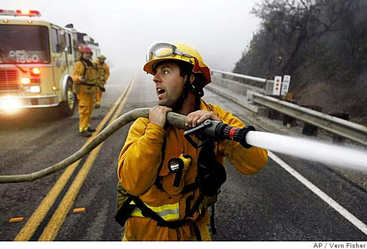 Rick Ronstadt, firefighter with the Garden Grove, Calif. fire department, works on the Basin Complex Fire on the east side of Highway One near Esalen Institute in Monterey County in Big Sur, Calif., on Monday, July 7, 2008. The fire has charred 117 square miles in the Big Sur area and was just 11 percent contained Monday. Officials said crews were burning out brush between the fire's leading edge and Big Sur's famed restaurants and hotels and cutting more lines to block flames creeping down from ridge tops. (AP Photo/Monterey County Herald, Vern Fisher)
