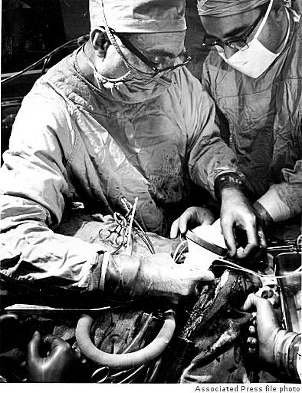 *** FILE *** Dr. Michael E. DeBakey, left, Baylor University Medical School heart surgeon, and one of his team of assistants, implants an artificial heart in patient Marcel L. DeRudder at Methodist Hospital in Houston, Texas, in this April 21, 1966 file photo. DeBakey, the world-famous cardiovascular surgeon who pioneered such now-common procedures as bypass surgery and invented a host of devices to help heart patients, died Friday night July 11, 2008 at The Methodist Hospital in Houston, officials announced. He was 99. (AP Photo, FILE)