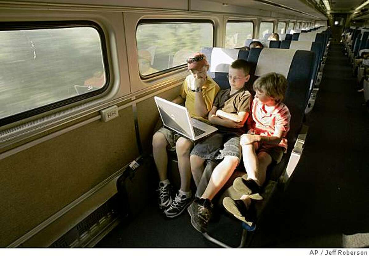 **ADVANCE FOR WEEKEND EDITIONS, SEPT. 8-9** Justin Braun, 12. left, Dylan White, 10, center, and younger brother Riley White, 8, use a computer as they travel toward Chicago, Monday, July 9, 2007, on Amtrak's Lincoln Service between St. Louis and Chicago. (AP Photo/Jeff Roberson)