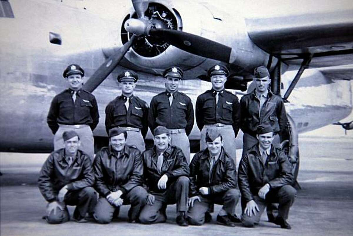 William Kalan (top row in the center) with his crew and their plane from World War II.