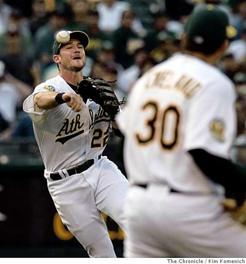 A's third baseman Jack Hannahan throws to first as pitcher Dana Eveland gets out of the way in the fifth inning as the Oakland Athletics play the Anaheim Angels at McAfee Coliseum on Saturday, July 12, 2008.Photo by Kim Komenich / The Chronicle Photo: Kim Komenich, The Chronicle