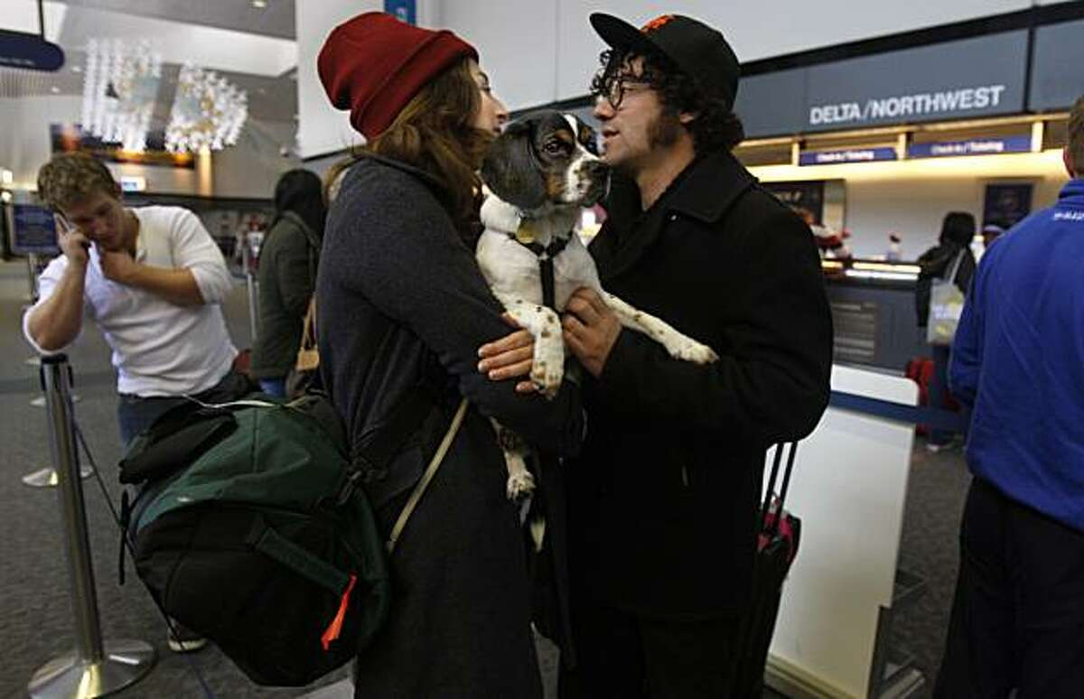Tess Patalano with her dog Ihu and M.G. Martin (right) from San Francisco as they wait in line to check in for their flight to New York at the San Francisco Airport on Monday, December 21, 2009. Californians expected to travel over the Christmas-New Year holidays are expected to rise this year.