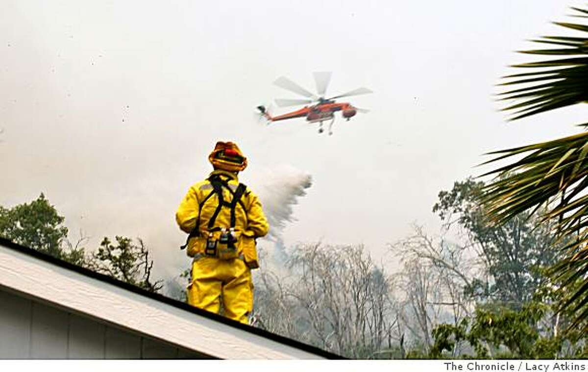 Brett Chairez of Healdsburg stands on the roof of Ken Fitchs' home as scout planes check on the visibility of the wildfire, Friday July 11, 2008, in Butte County, Yankee Hill, Calif.Photo by Lacy Atkins /The Chronicle