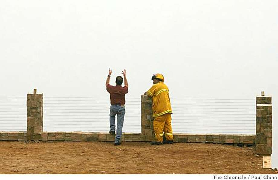 Resident Sep Carola and San Francisco firefighter Don Durkee look into the smoke-filled Feather River Canyon at a neighbor's home in Paradise, Calif., on Thursday, July 10, 2008.Photo by Paul Chinn / The Chronicle Photo: Paul Chinn, The Chronicle