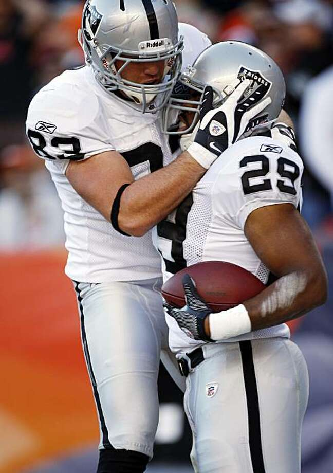 Oakland Raiders running back Michael Bush is congratulated by teammate Brandon Myers after running for a touchdown during the second quarter against the Denver Broncos at Invesco Field at Mile High in Denver on Sunday. Photo: Jack Dempsey, AP