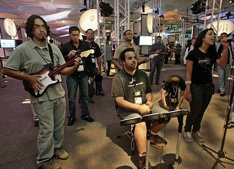 """Renelly Morel, right, joined by two other attendees, play """"Rockband,"""" a music/rhythm video game, at the E3 Media and Business Summit Tuesday, July 15, 2008, in Los Angeles. (AP Photo/Ric Francis) Photo: Ric Francis, AP"""