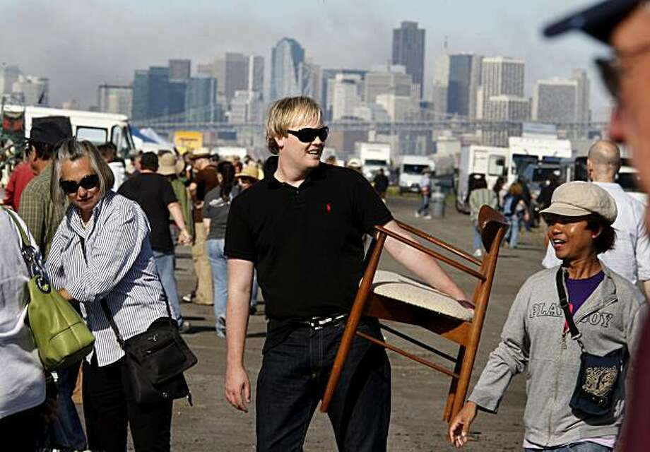 With the fog clearing and San Francisco in the background, Gibson (center) carries his new found chair around the fair. Interior designer Grant K. Gibson often shops for thrift-store finds at the Alameda Point Antiques and Collectibles fair in Alameda, CA. Photo: Brant Ward, The Chronicle