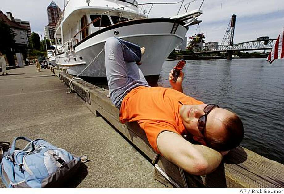 """Tim Ferriss relaxes in downtown Portland, Ore., Friday, June 20, 2008. Ferriss, author of """"The Four-Hour Workweek,"""" uses what he calls a """"small army"""" of virtual assistants for everything he can think of checking his e-mail, screening his phone calls, and sending gifts to family and friends. He has even had a team find and schedule dates for him online. (AP Photo/Rick Bowmer) Photo: Rick Bowmer, AP"""