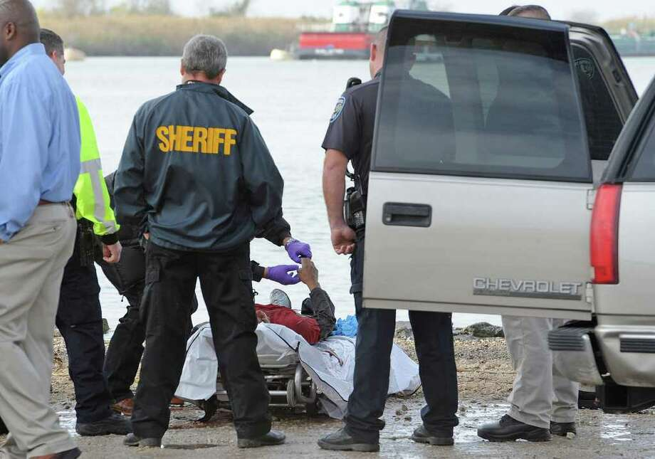 Emergency officials examine the body of a man that was found Monday morning near the Intracoastal Bridge on Texas 87. An investigation into the incident is underway. Photo taken Monday, December 19, 2011 Guiseppe Barranco/The Enterprise Photo: Guiseppe Barranco, STAFF PHOTOGRAPHER / The Beaumont Enterprise