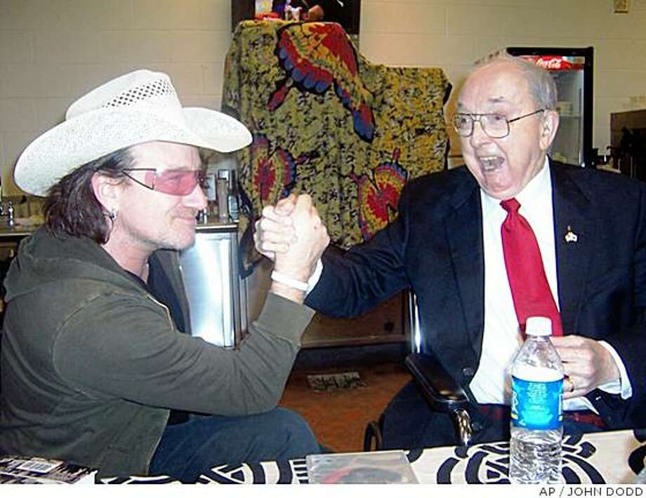 **FILE** This Monday, Dec. 12, 2005 file photo, supplied by the Jesse Helms Center shows Bono, left, of the Irish rock band U2 and former North Carolina Sen. Jesse Helms  share a greeting at a pre-concert meal at the new Charlotte Bobcats Arena in Charlotte, N.C., before U2 played to a crowd of 17,000. Former Sen. Jesse Helms, who served 30 years in Congress, died on the Fourth of July, the Jesse Helms research center says. He was 86.  (AP Photo,Jesse Helms Center,John Dodd, File ) Photo: JOHN DODD, AP