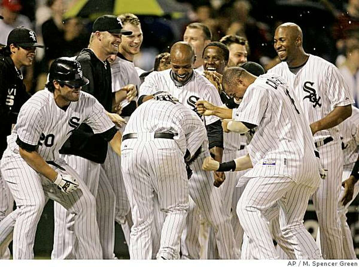 Chicago White Sox's A.J. Pierzynski, center is mobbed by teammates after hitting the game-winning home run against the Cleveland Indians during the 10th inning of a baseball game Wednesday, July 2, 2008, in Chicago. The White Sox defeated the Indians 6-5. (AP Photo/M. Spencer Green)