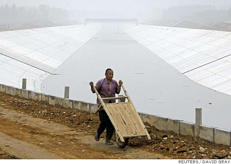 A worker pushes a cart along the banks of a section of the uncompleted Beijing-Shijiazhuang canal near the town of Baoding in Hebei Province, located around 120 kilometres (70 miles) south of Beijing June 25, 2008. The canal, part of the mammoth US$25 billion South-to-North Water Diversion scheme, aims to bring water from southern rivers to the arid north to bolster Beijing's scarce water supplies for the 2.5 million visitors expected during the 2008 Olympic Games. But China's ambitious hopes for a 'green' Olympics have magnified, not relieved, the city's reckless dependance on water for strained underground supplies and the mammoth canal project says Probe International, a Canada-based conservation group. Picture taken June 25, 2008.     REUTERS/David Gray     (CHINA) Photo: DAVID GRAY, REUTERS