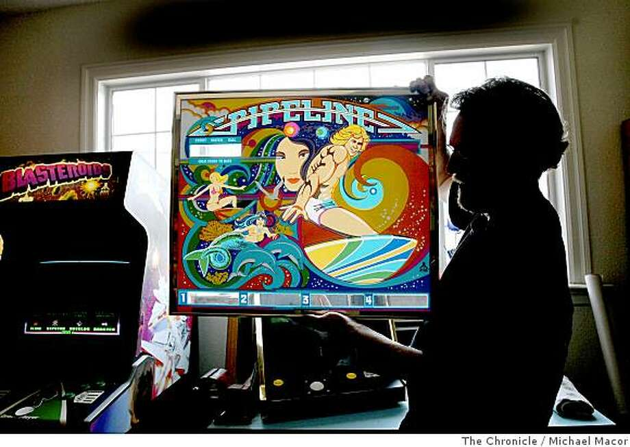 "Dale Luck, holds a ""back glass"" from a 1983 pinball game called, Pipeline, that was never went into production. Just a small part of his collection shown at his home in Campbell, Calif. on July 11, 2008. Photo By Michael Macor/ The Chronicle Photo: Michael Macor, The Chronicle"