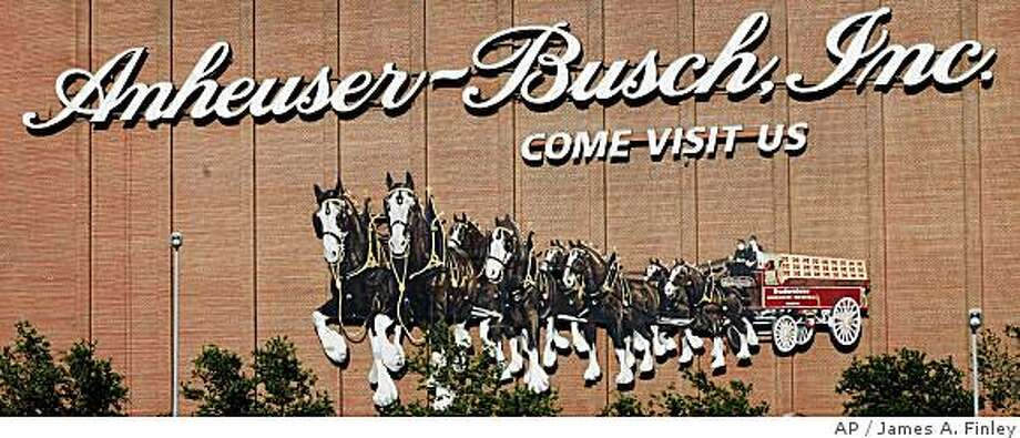 ** FILE ** In this June 11, 2008 file photo, a display along one of the buildings in the Anheuser-Busch brewery complex shows Clydesdales pulling a hitch of Budweiser products in St. Louis, Mo. Anheuser-Busch reportedly has agreed to be acquired by Belgian brewer InBev for $49.9 billion. The deal being reported by The Wall Street Journal would create the world's largest brewer and put the iconic American beer maker in the hands of the Belgian-based company behind Stella Artois and Beck's beers. (AP Photo/James A. Finley, file) Photo: James A. Finley, AP